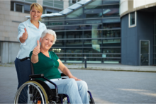 Caregiver with female elder in wheelchair